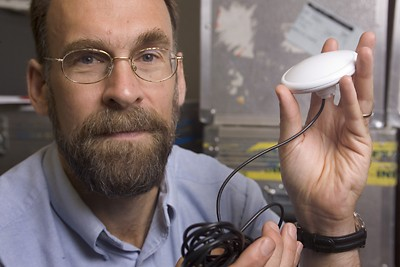 Mark Psiaki, Cornell associate professor of mechanical and aerospace engineering, holds a palm-sized patch antenna.