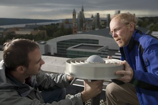 Graduate student Alessandro Cerruti, left, and Professor Paul Kintner work on the antenna on the roof of Phillips Hall. They have found that the kinds...