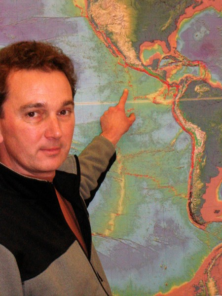 University of Oregon geologist Douglas Toomey points to the map to show where in the Pacific Ocean his team has been investigating volcanic plumbing and the formation of hydrothermal vents on the ocean floor.