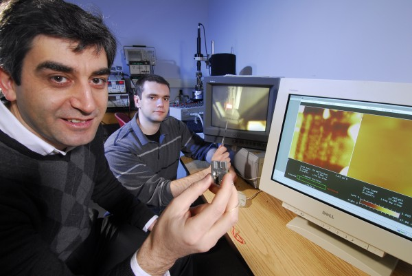Levent Degertekin (left), a professor in the George W. Woodruff School of Mechanical Engineering at Georgia Tech, shows the adapted AFM holder while graduate student Guclu Onaran points to an image of the FIRAT probe scanning a sample. The front monitor displays the topography of a sample obtained by the FIRAT probe at a speed of 2 frames per second, which is nearly 100 times faster than the normal speed.