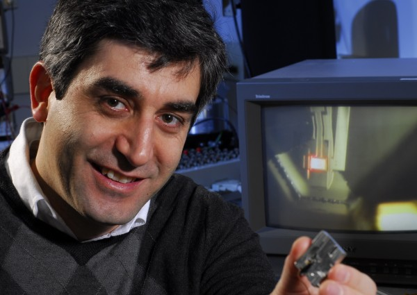 Levent Degertekin, a professor in the George W. Woodruff School of Mechanical Engineering at Georgia Tech, shows the adapted AFM holder. The monitor shows an image of the FIRAT probe scanning a sample as seen through the AFM system's optical camera.