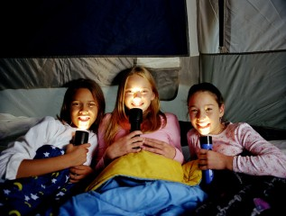 Girls with flashlights camping out