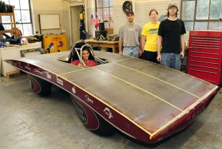 Matt Martin takes his place in the driver's seat of Sol Invictus, Iowa State University's solar race car. In the back, left to right, are Team PrISUm members...
