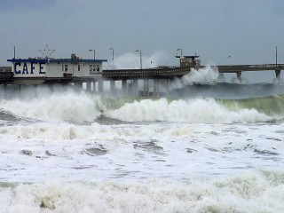 Waves at high tide inundate Ocean Beach Pier during a 2000 storm. Researchers say sea level rise presents its greatest danger when water level spikes caused...