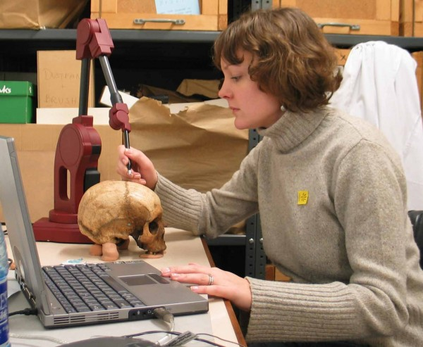 Dr. Karen Baab of Stony Brook University working in her lab on a modern human skull.