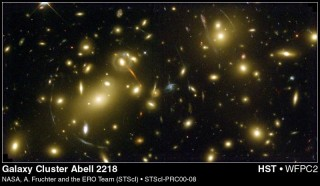 The gravity of galaxy cluster Abell 2218 bends and focuses the light from galaxies that lay behind it in this Hubble Space Telescope image. The effect...