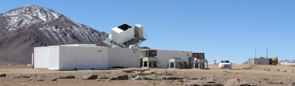 The QUIET experiment in operation in the Atacama Desert. The receiver in the mount on the roof of the building rapidly scans the sky, looking for radiation emitted shortly after the birth of the universe.