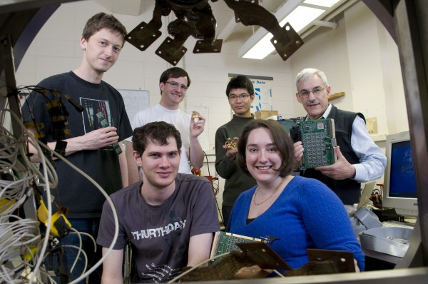 Here QUIET team members display circuitry and components developed for the detection of gravity waves: physics graduate students Immanuel Buder and Alison Brizius (front row); Colin Bischoff, physics graduate student; David Moore, undergraduate in physics; Akito Kusaka, postdoctoral fellow in the Kavli Institute for Cosmological Physics; and Bruce Winstein, the Samuel K. Allison Distinguished Service Professor in Physics (back row, l-r).