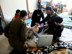 Shinji Tsunawaki, M.D., (masked) of the U-M affiliated Shizuoka Family Medicine program, assesses a pregnant woman who was stranded in a remote area following...