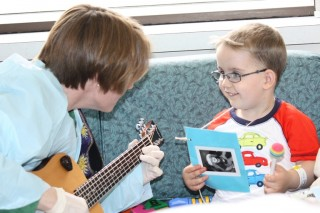 Lori Gooding worked with spina bifida patient Joshua Divens earlier this year during a music therapy session at Kentucky Children's Hospital.