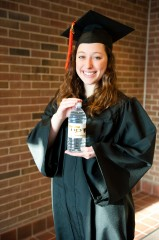 Michigan Tech student Emily Baker tries on a recyclable cap and gown made from empty plastic water bottles.
