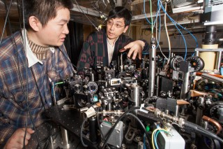 Graduate student Xibo Zhang (left) and Cheng Chin (right), associate professor in physics, examine experimental hardware in Chin's ultracold laboratory...