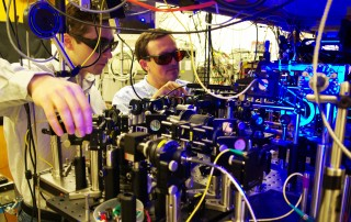 Georgia Tech graduate student Yaroslav Dudin and professor Alex Kuzmich (l-r) adjust optics as part of research into the production of single photons for use in optical...
