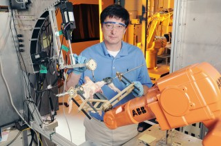 Gary McMurray, chief of the Georgia Tech Research Institute's Food Processing Technology Division, poses with the Intelligent Cutting and Deboning System,...
