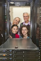 Pictured are the team of Stony Brook researchers from the Department of Physics and Astronomy by the Njal supercomputer cluster, a small Beowulf cluster...