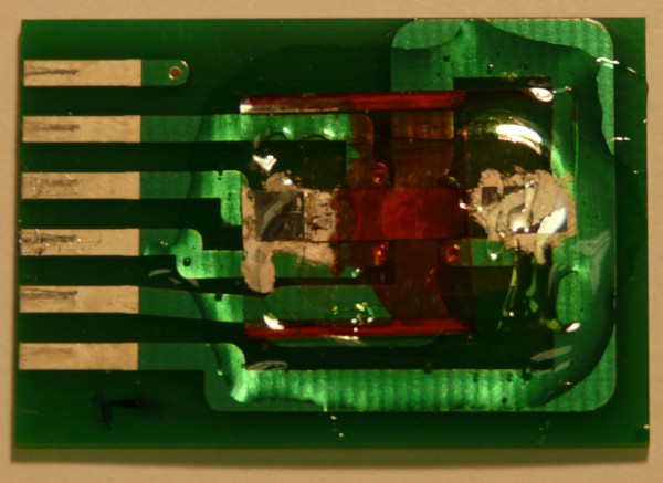 "An inexpensive and highly accurate ""spintronic"" magnetic field sensor developed at the University of Utah is shown here. The entire device, on a printed circuit board, measures about 0.8 inches by 1.2 inches. But the part that actually detects magnetic fields is the reddish-orange thin-film semiconductor – essentially ""plastic paint"" – near the center-right of the device."