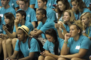 Students at the University of North Carolina Wilmington use their cell phones to post to social media sites and text during a basketball game.