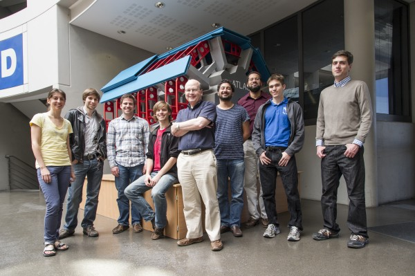 During a recent visit to CERN, James Pilcher, professor in physics (center), posed for this photograph with other members of the UChicago ATLAS Group. They stand in front of a miniature model of the ATLAS detector.