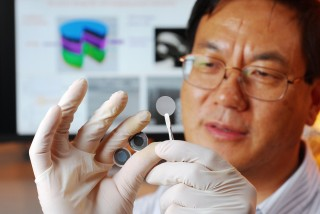 Georgia Tech researcher Zhong Lin Wang holds the components of a new self-charging power cell that uses piezoelectric materials to directly convert mechanical...