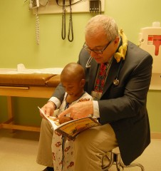 Ken Haller, M.D., associate professor of pediatrics at Saint Louis University reads 'The Littlest Pumpkin' to his patient Malik Vaughn at SSM Cardinal...