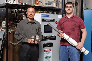 Iowa State University engineers Song-Charng Kong, left, and Nicholas Creager are studying a new bio-oil gasifier. Kong is holding samples of bio-oil that...