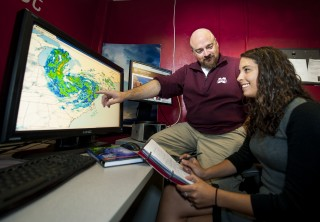Mike Brown, Mississippi State University associate professor of meteorology and climatology, works with broadcast meteorology student Rachel Kroot, of Lancaster,...