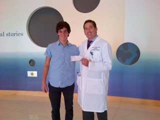 Cameron Cohen (L), a 14-year-old app creator and philanthropist, recently donated a check to UCLA's Dr. Noah Federman to support his pediatric cancer research....