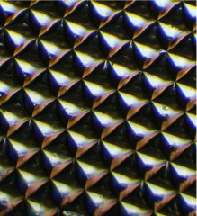 Microscopic image of a silk optical implant created when purified silk protein is poured into molds in the shape of multiple micro-sized reflectors and then...