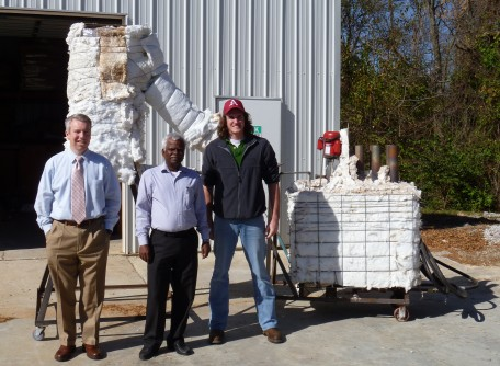 Panneer Selvam, center, Micah Hale, left, and Matt Strasser display the thermocline energy storage test system outside the Engineering Research Center in south Fayetteville.