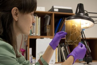 Heather Brown, a second-year art conservation graduate student at UD, examines an early cellulose acetate film negative likely damaged by exposure to high...