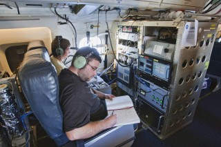 Terry Lathem, a graduate student in Georgia Tech's School of Earth and Atmospheric Sciences, takes notes aboard a NASA DC-8 gathering samples of microorganisms...