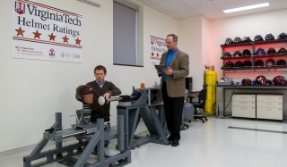 Left to right, Steven Rowson and Stefan Duma, both of the Virginia Tech – Wake Forest University School of Biomedical Engineering and Sciences, fit a hockey...