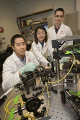 Dr. Jonathan T.C. Liu, left, around a high-powered microscopy system in his Biomedical Engineering laboratory that is used to test a new brain-tumor targeting...
