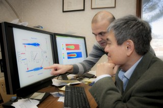 Doctoral candidate Omid Samimi, left, and Dr. C. P. Chen discuss their computer simulation of evaporating fuel sprays.
