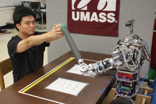 Computer science doctoral student Hee-tae Jung practicing therapeutic arm movement with a uBot5 personal robot at UMass Amherst.