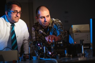 Arash Mafi (left), associate professor of electrical engineering, consults with his doctoral student Salman Karbasi. Karbasi designed an optical fiber...