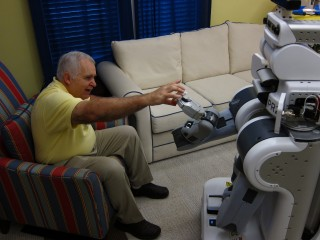 A robot assists a patient with a medication bottle