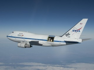 With the large door over its 2.5-meter German-built telescope wide open, NASA's Stratospheric Observatory for Infrared Astronomy 747SP aircraft soars...