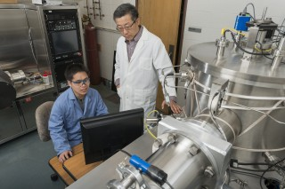University of Delaware professor John Xiao (standing) and research associate Xin Fan work with the high vacuum magnetron deposition system, which is used...