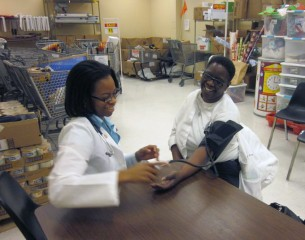 As part of SNMA's Community Health Coalition, SLU second-year medical student Michelle Hall checks the blood pressure of a customer at a local grocery...