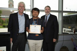 Yufeng Xin of RENCI's networking research group (center), receives an award at the U.S. Ignite Applications Summit from Glenn Richart (left), founder...