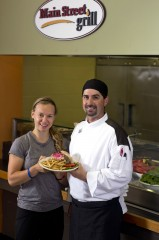Campus Executive Chef Kyle Mayette (right) serves a grilled free-range chicken breast platter to student Jenna L. Boss '15 of Little Canada, Minn.