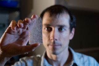 Vasilii Petrenko, assistant professor of earth and environmental sciences, holds a 50,000-year-old ice sample from Taylor glacier in Antarctica.