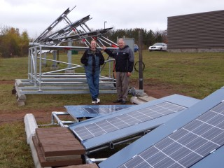 Michigan Tech solar energy scientist Joshua Pearce, left, and Jay Meldrum, director of the Keweenaw Research Center, with the array of solar panels behind...
