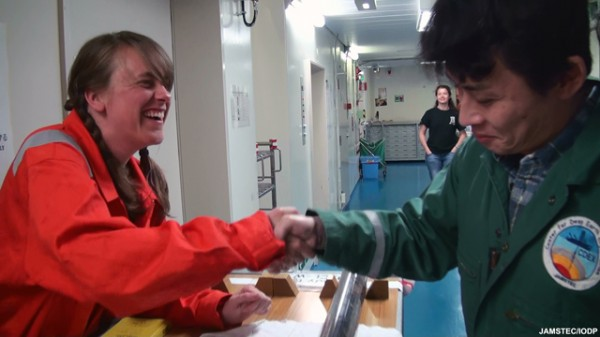 Scientists Christie Rowe (left) of McGill University and Kohtaro Ujiie of Tsukuba University, aboard the Chikyu, celebrated with a handshake when they agreed they had found the ocean-floor fault in the drill core.