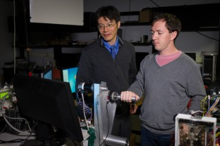 "Using arm sensors that can ""read"" a person's muscle movements, Georgia Institute of Technology researchers (Professor Jun Ueda, left, and Billy Gallagher)..."