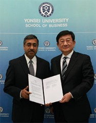 Mahendra R. Gupta, Dean of Olin Business School, and Young-Ryeol Park, Dean of Yonsei School of Business, hold the official agreement between their schools...