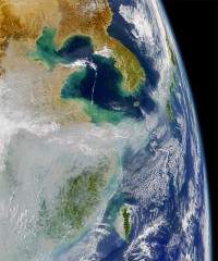 Satellite photo shows  huge air pollution clouds at far left.   Japan is on the right.
