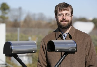 Patrick Gatlin with a Parsivel2, a disdrometer that measures the particle size and velocity of raindrops falling through a laser, at UAH's weather monitoring...
