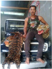 One of the tiger traders before his arrest showing off a tiger skin and a stuffed tiger head.